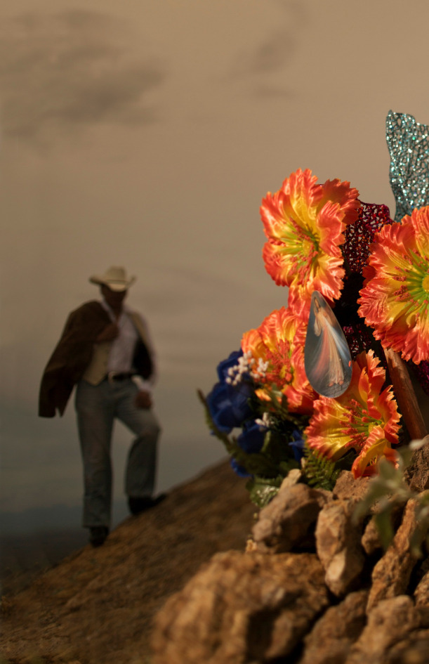 Cowboy and flowers on grave ©